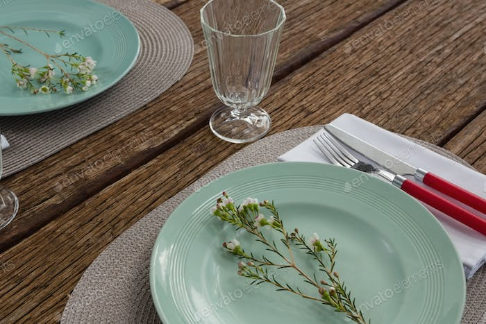Fork and butter knife with napkin and flower on plate