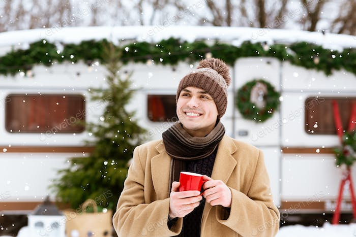 Handsome Young Man With Red Coffee Cup Standing Outdoors At Winter Campsite