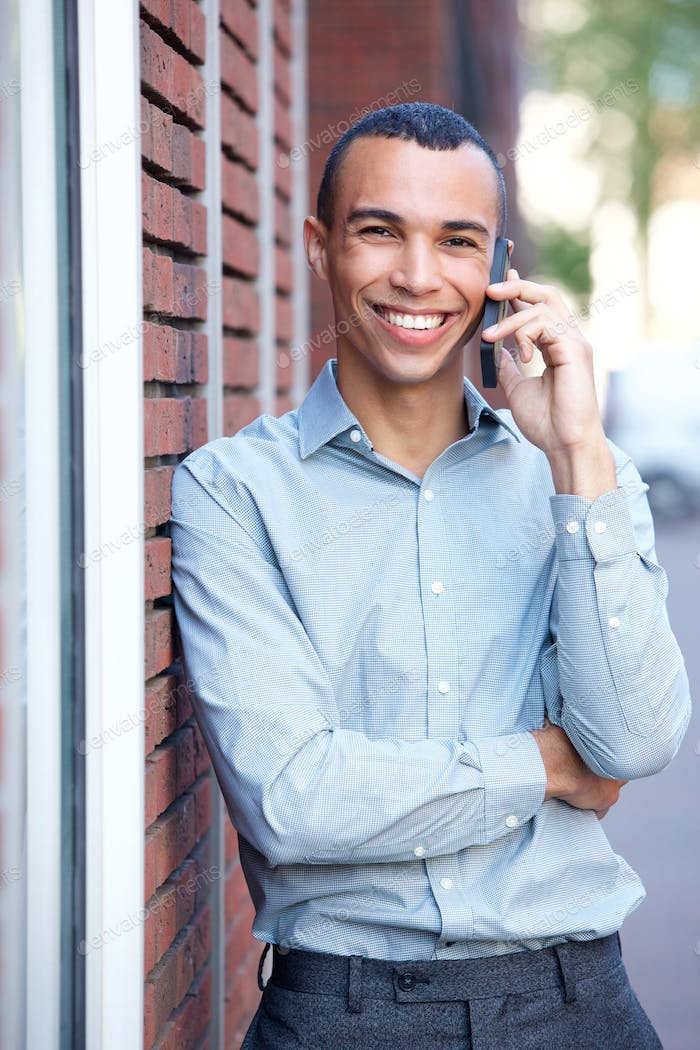 happy young businessman talking on mobile phone
