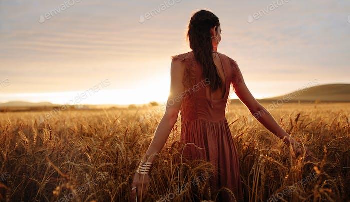 Unbeschwerte Frau schlendern im Weizenfeld