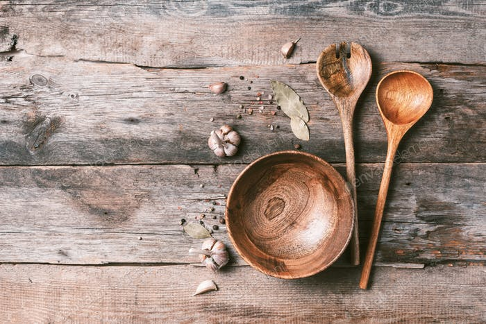 Various kitchen wooden utensils on wood background. Top view. Copy space. Bowl and spoons, spices