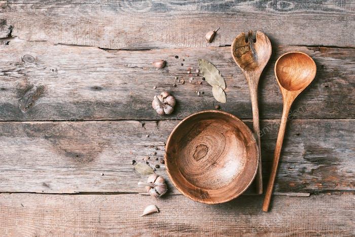 Verschiedene Küchenhelfer aus Holz auf Holzhintergrund. Draufsicht. Kopierraum. Schüssel und Löffel, Gewürze
