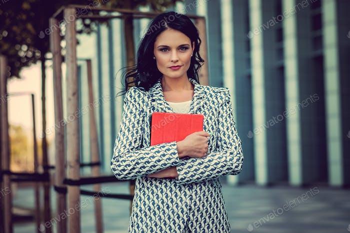 Брюнетка деловая женщина держит планшетный компьютер.