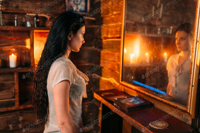 Young woman at the mirror on spiritual seance