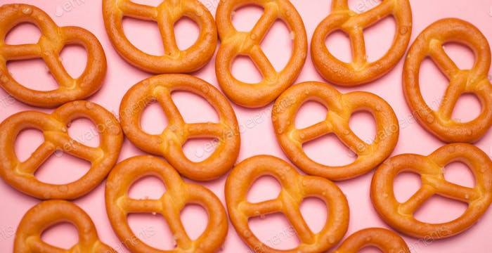 photo pattern of many crispy pretzels bakery on pink background
