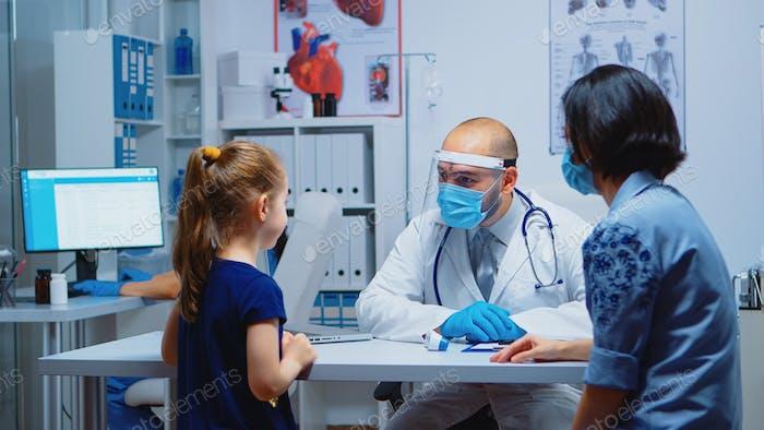 Specialist medic measuring child temperature