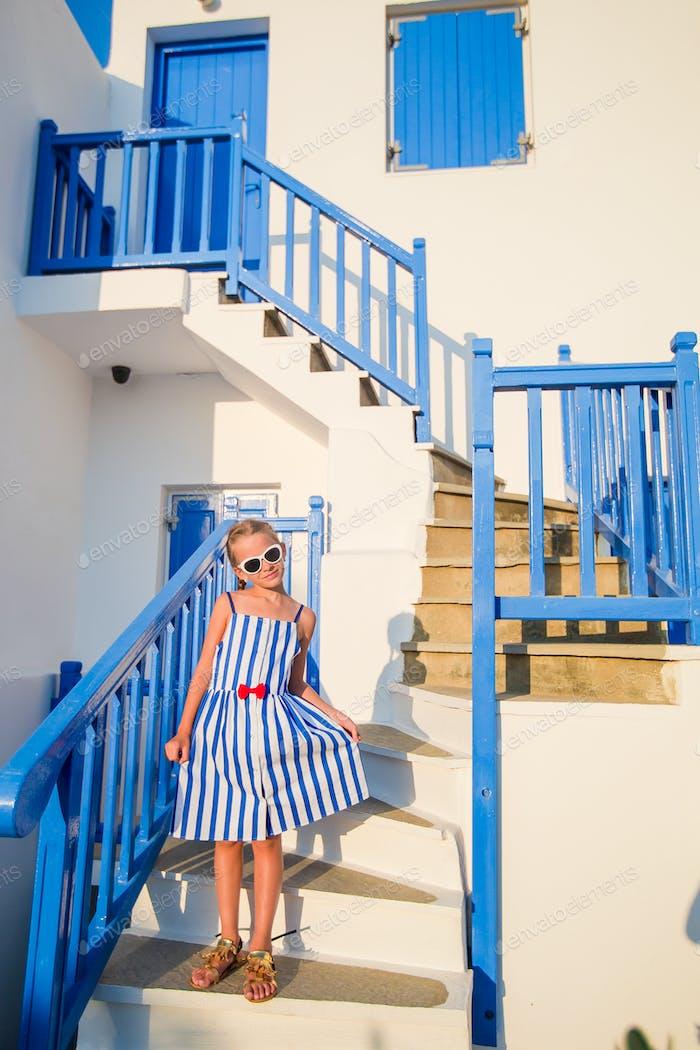 Niedliches Mädchen in blauem Kleid auf der Straße des typischen griechischen traditionellen Dorfes auf Mykonos Insel, in Griechenland