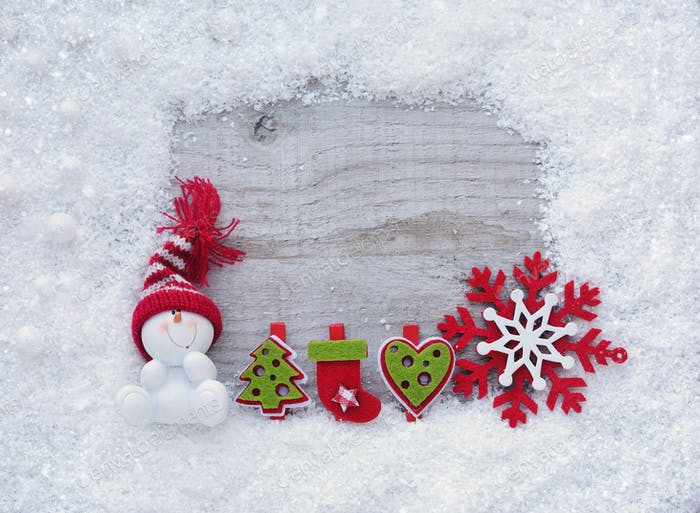 Frame of snow with snowmen and christmas decorations on wooden b