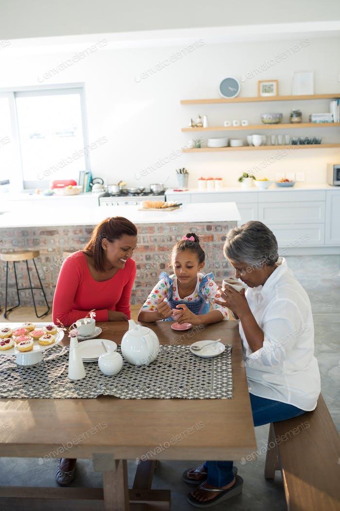 Multi-generation family having breakfast in dining table