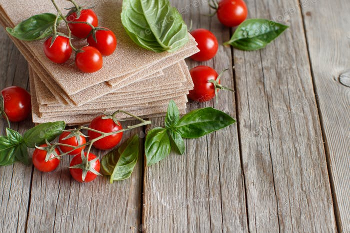 Raw lasagna sheets,basil and cherry tomatoes
