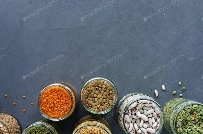 Dried legumes in storage jars on mottled blue