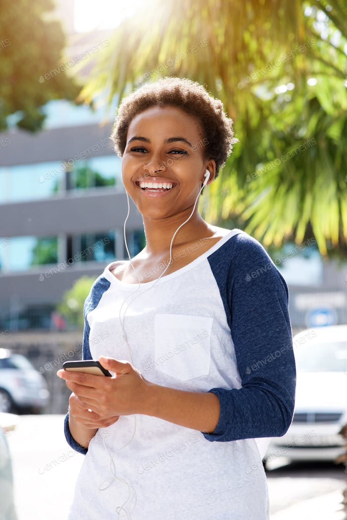 Young woman listening to music with earphones and mobile phone