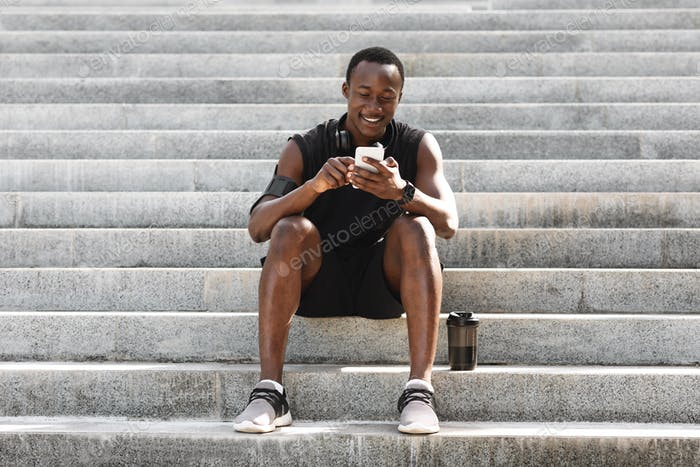 Break In Training. Athlete Black Guy Resting On Steps With Smartphone