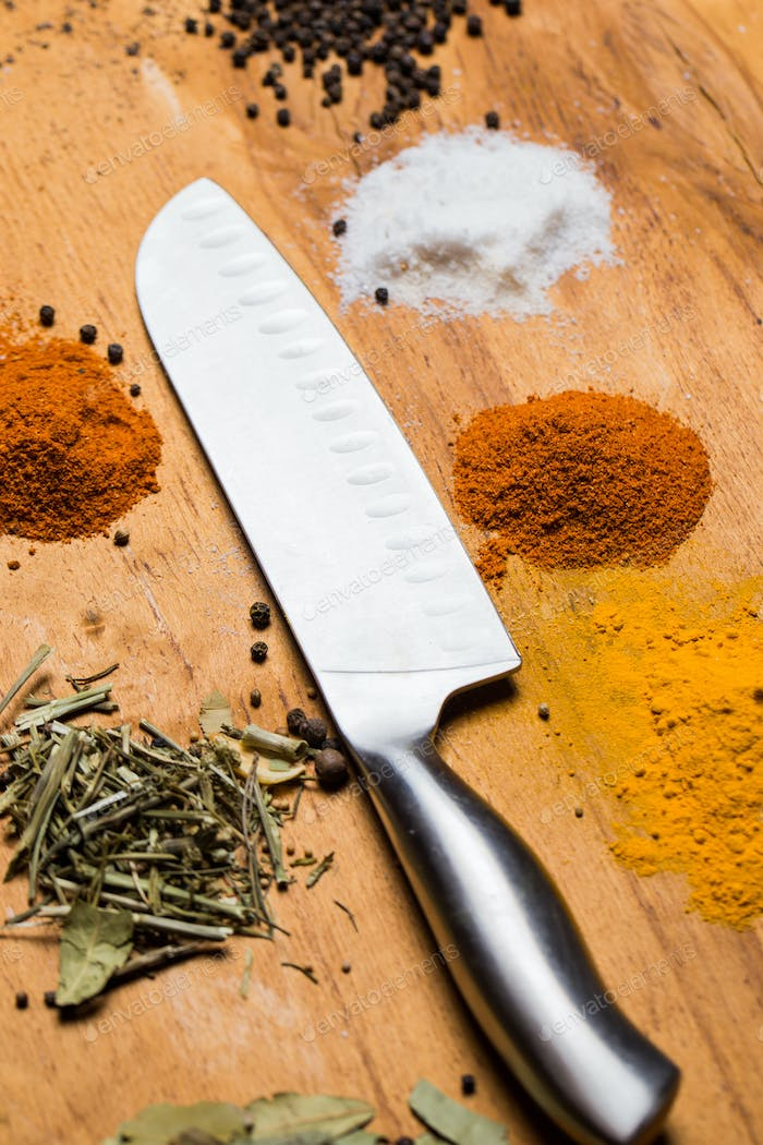 Spoon, knife and heap of spices on the table