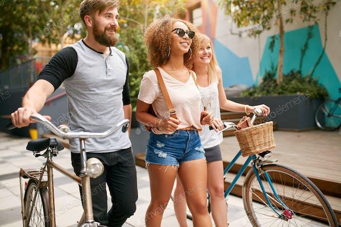 Drei Freunde mit Fahrrädern, die Spaß auf einer Straße haben