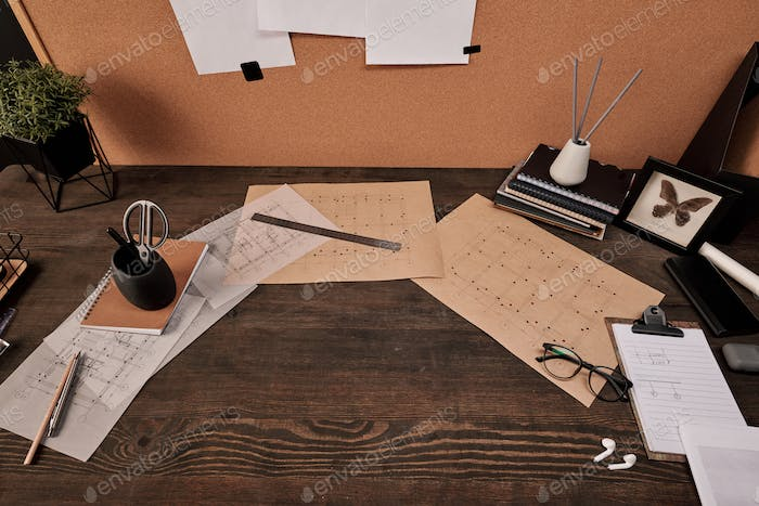 Blueprints, copybooks and office supplies surrounding copyspace on wooden table