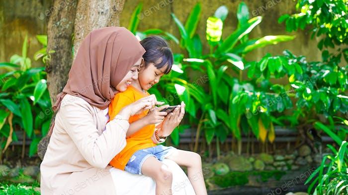 Мать играет с дочерью в парке