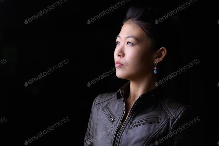 Face of beautiful Asian rebellious woman thinking outdoors at night