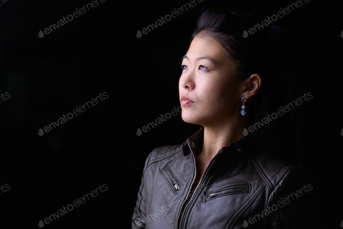Gesicht der schönen asiatischen rebellischen Frau denken im Freien in der Nacht