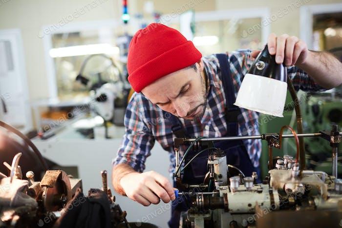 Worker Repairing Machines at Factory