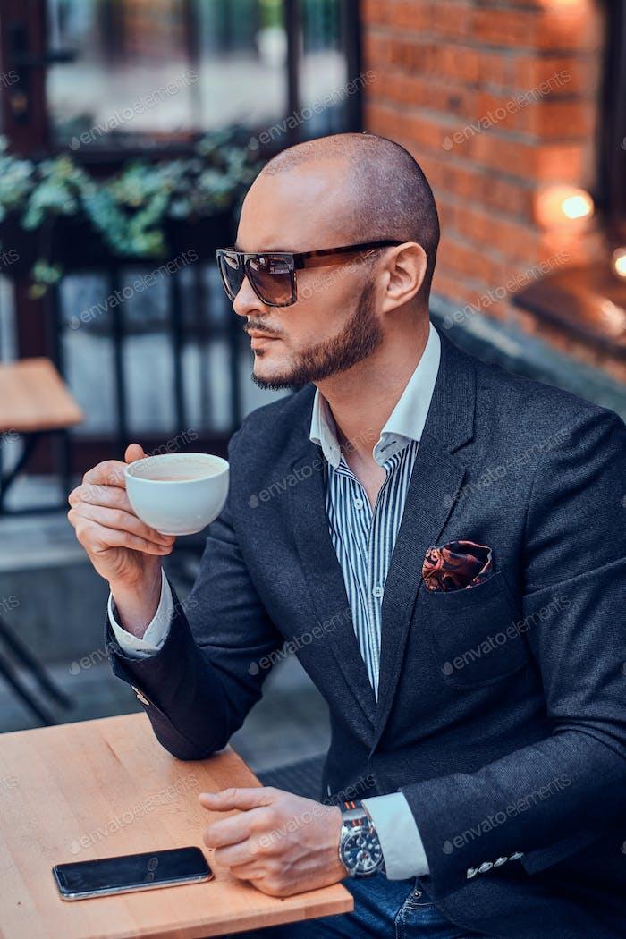 Thumbnail for Привлекательный элегантный бизнесмен сидит в кафе