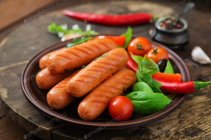 Grilled sausages and vegetables on a wooden background in rustic style.