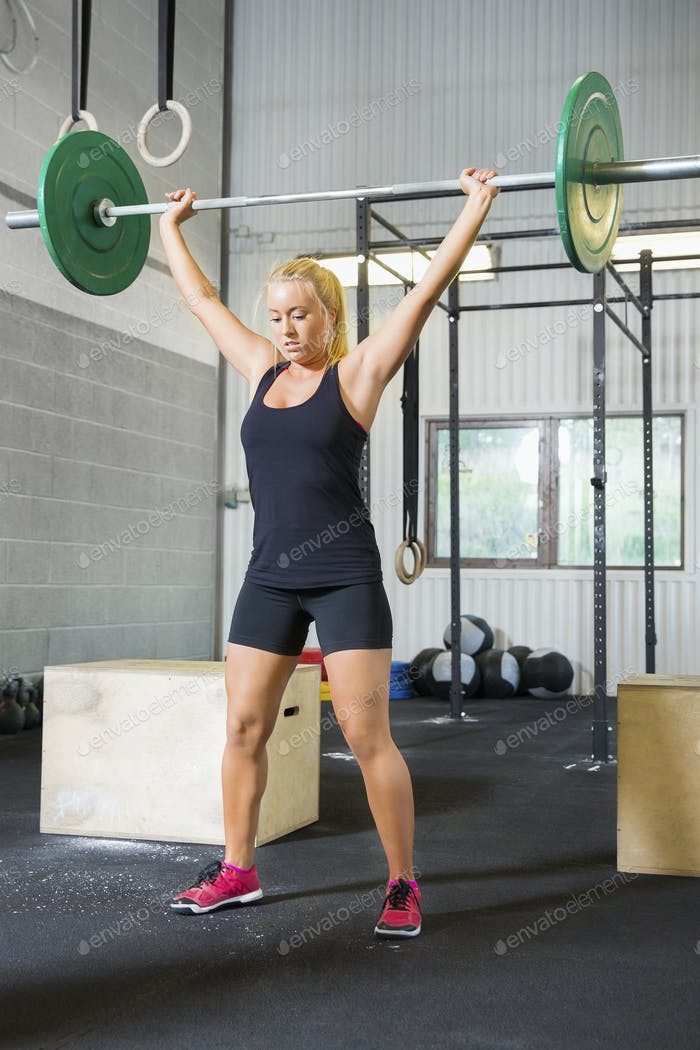 Determined Female Athlete Lifting Weights In Health Club