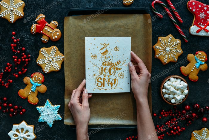 cropped view of hands with homemade gingerbreads and Let it snow greeting card on baking tray