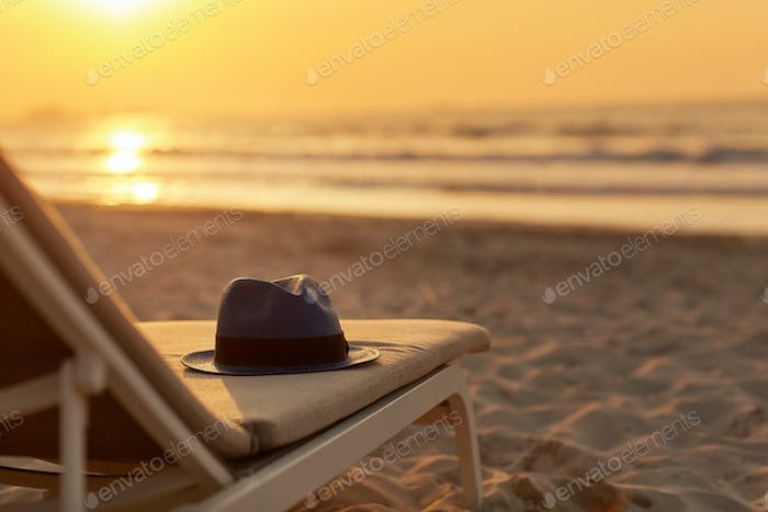 Blue hat lies on a sun lounger on a sandy beach by the sea in the rays of the setting sun