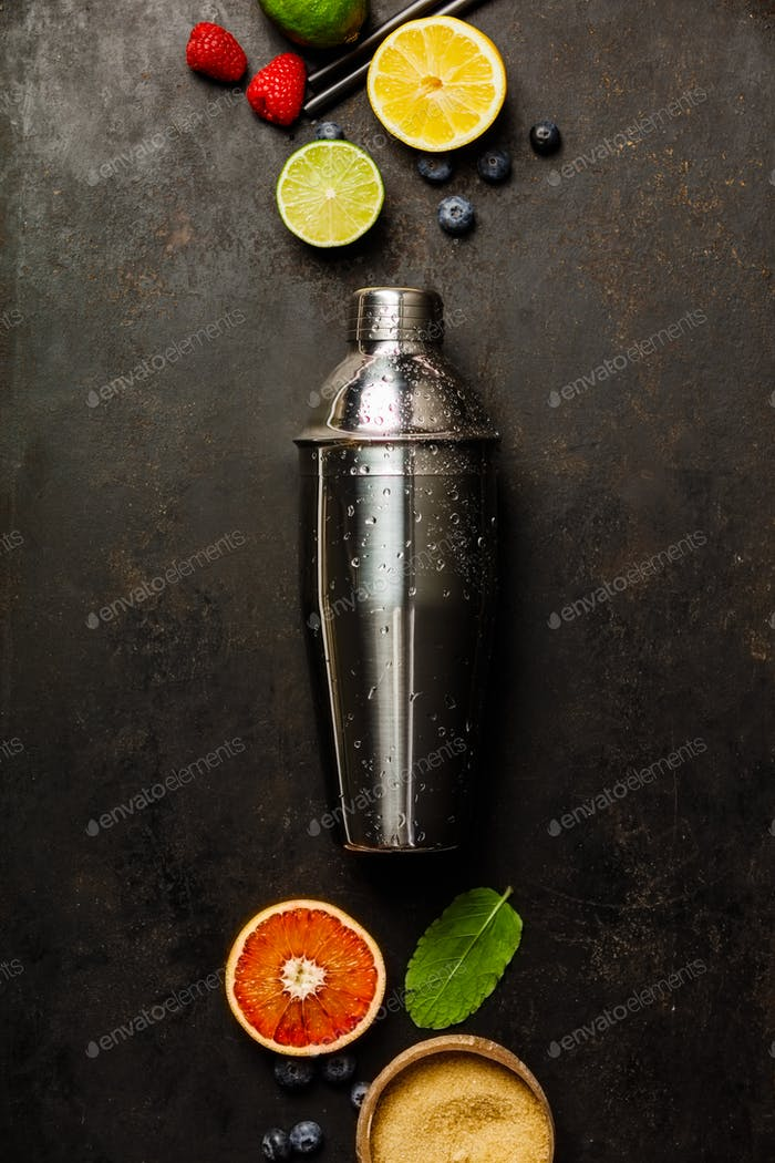 Cocktail shaker, tropical fruits and leaves on a dark background