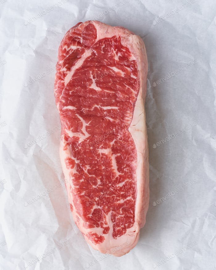 Big whole piece of raw beef meat, striploin on white parchment paper, zero waste packing.