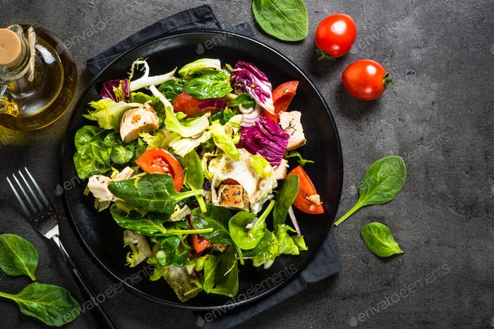 Green salad with chicken and vegetables on black