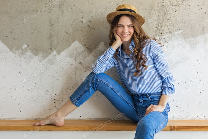 young attractive stylish woman sitting at wall background, straw hat