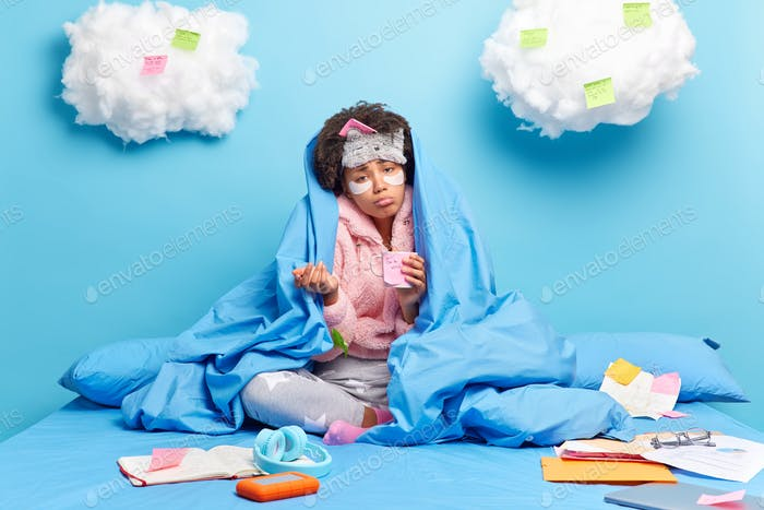 Photo of sad curly ethnic woman drinks coffee wrapped in blanket poses crossed legs on comfortable b