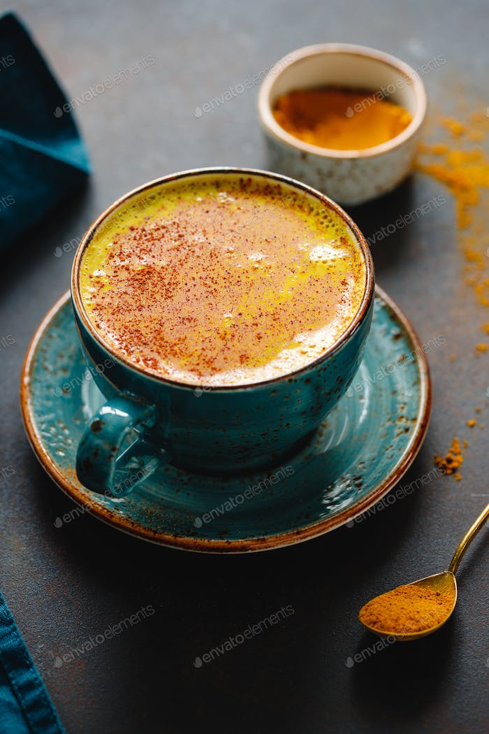 Closeup view of turmeric latte cup on a textured dark background.