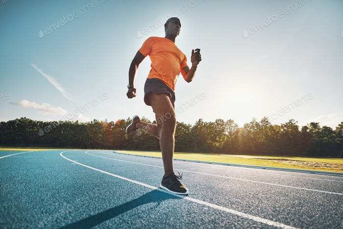 Dedicated young athlete running alone on a race track