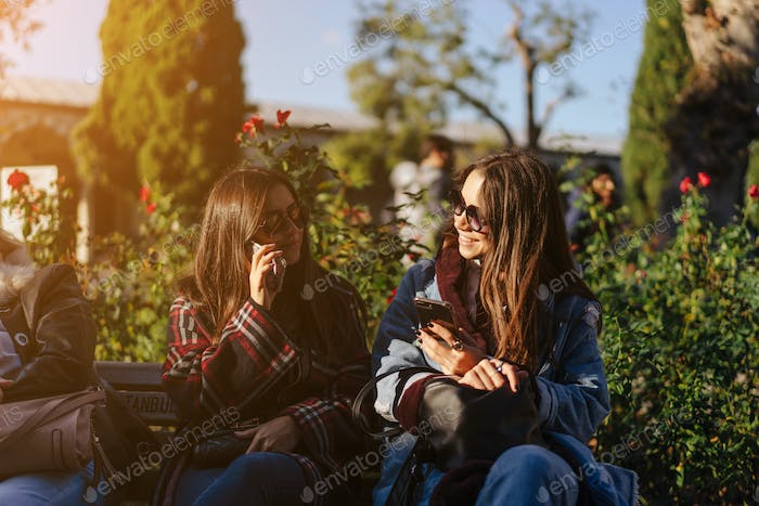 Two girls are resting on the bench