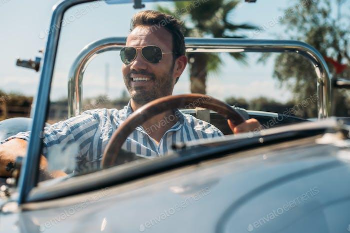 Man driving a convertible vintage car