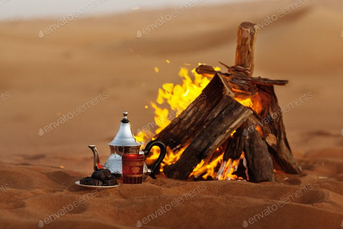 Dates, teapot, cup with tea near the fire in the desert with a beautiful background