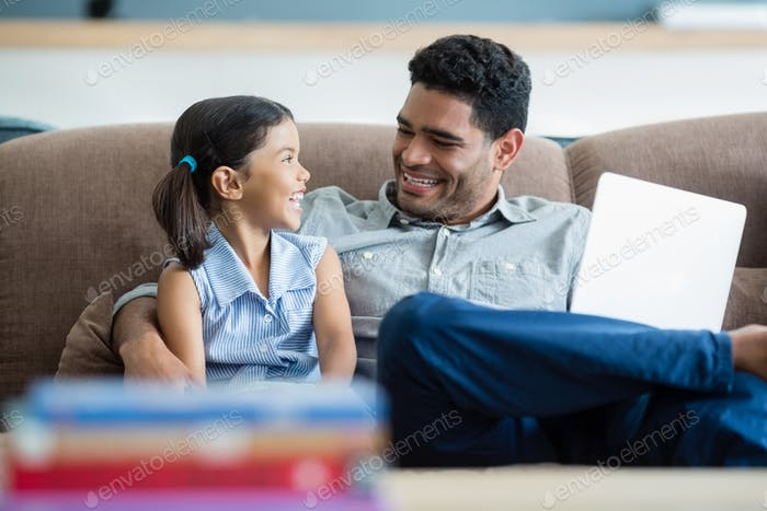 Father and daughter interacting on sofa in living room