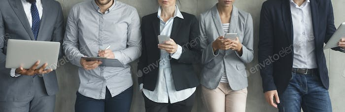 Businesspeople with phones and laptops over grey wall