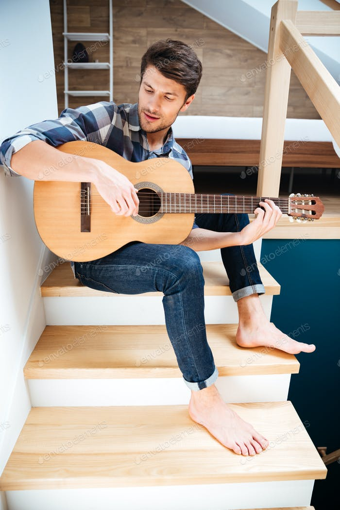 Man with guitar sitting indoors