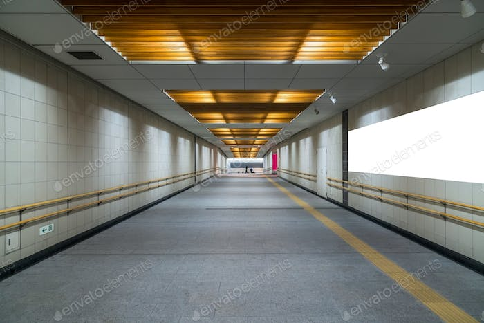 Walkway with Blank billboard located in underground hall or subway for advertising