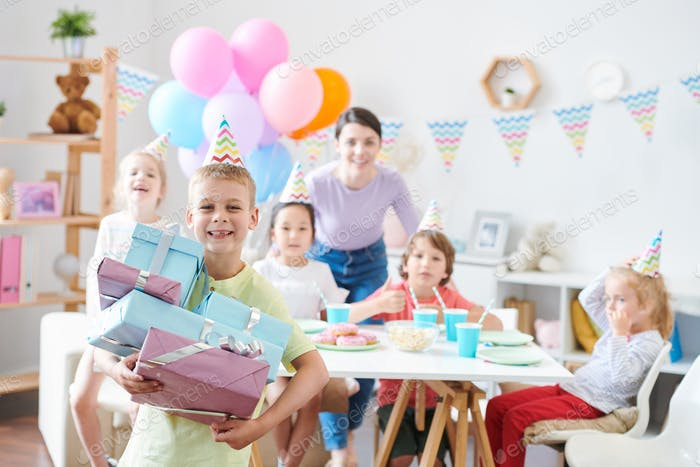 Cheerful little boy with stack of giftboxes standing in front of camera