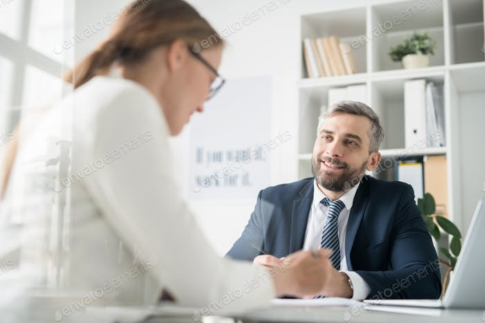 Happy businessman discussing work issues with colleague