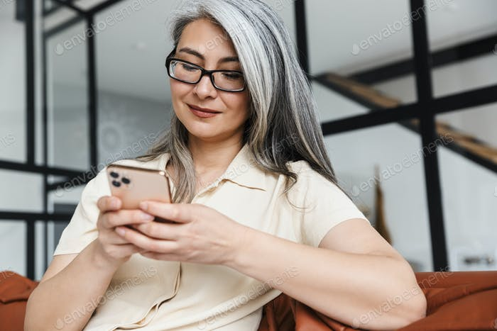 Positive cheery business woman sitting on sofa