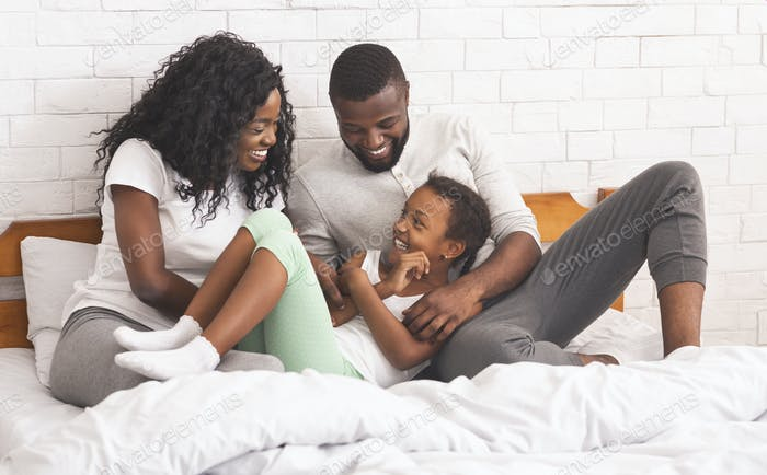 Black parents tickling their daughter while lying in bed together