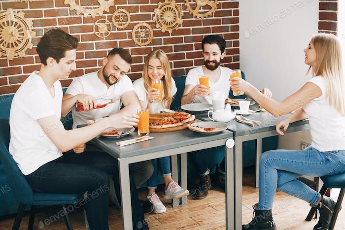 Cute friends in a cafe eatting a pizza