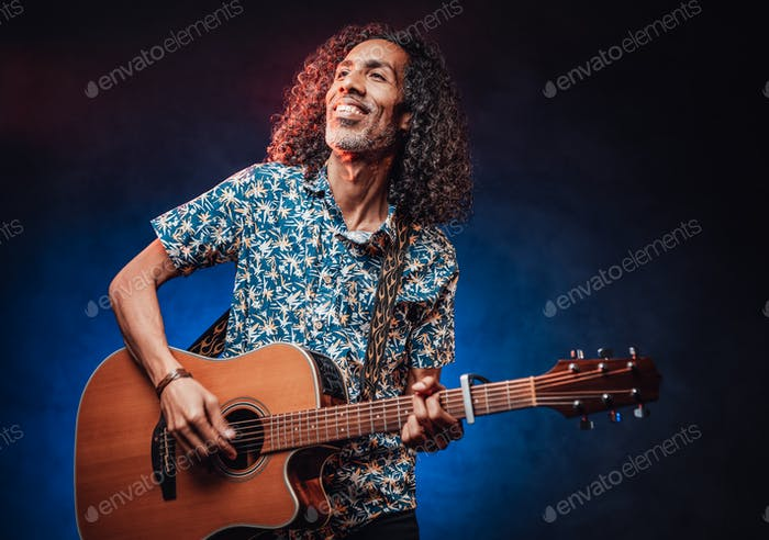 Happy middle aged hispanic musician singing and playing guitar on a dark