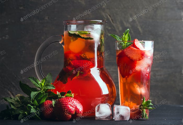 Homemade mint strawberry lemonade on dark wooden background